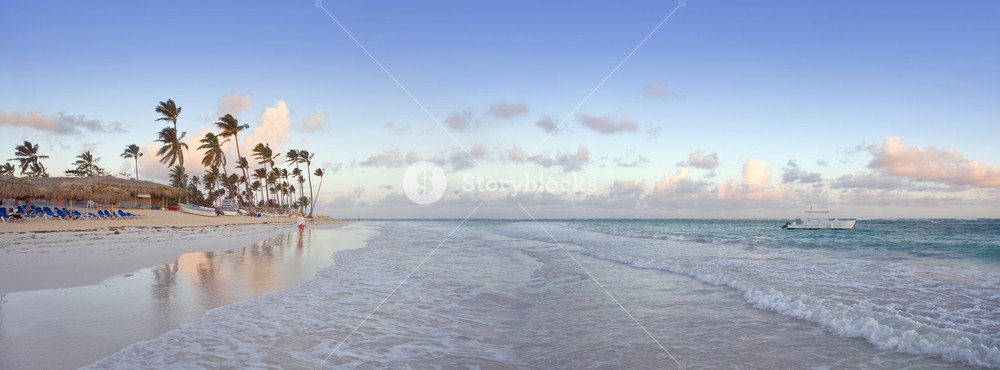 White boat and a tropical beach resort at sunset