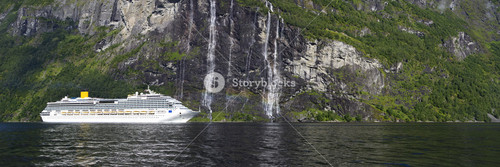 White cruise ship traveling past a rocky waterfall