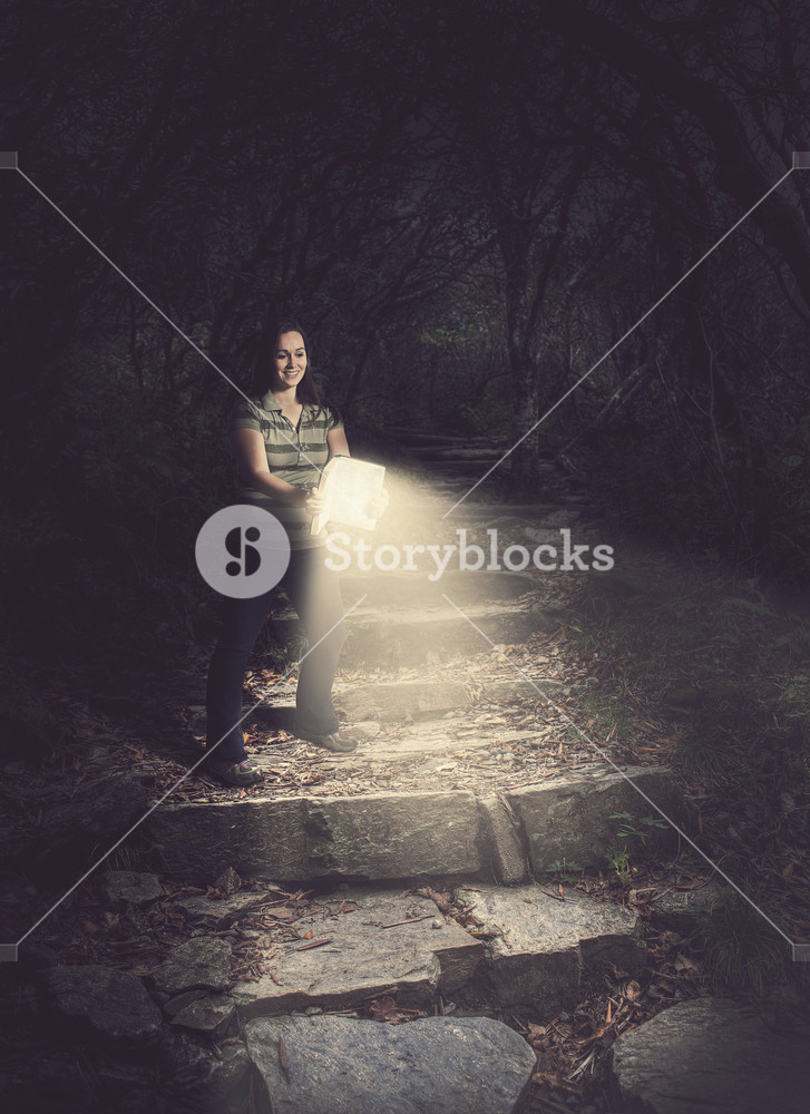 Woman holding a glowing Bible in the forest.