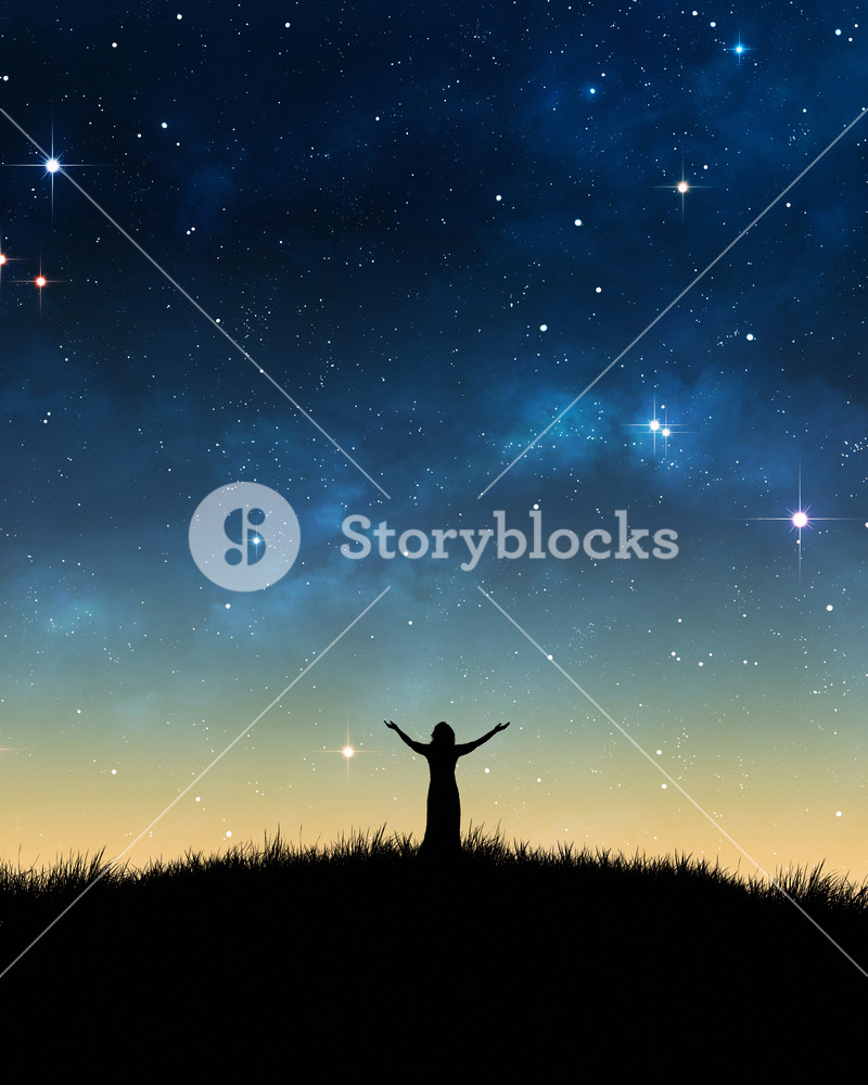 Woman in field with her hands lifted in praise