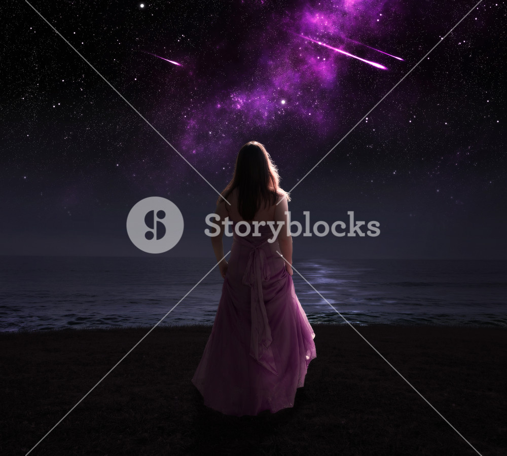 Woman standing in dress at night watching shooting stars.