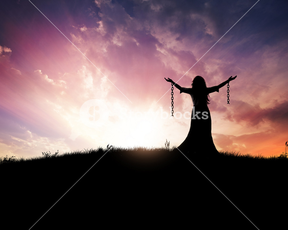 Woman standing with broken chains