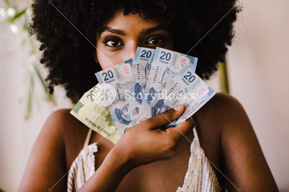 African American woman holding money to her face