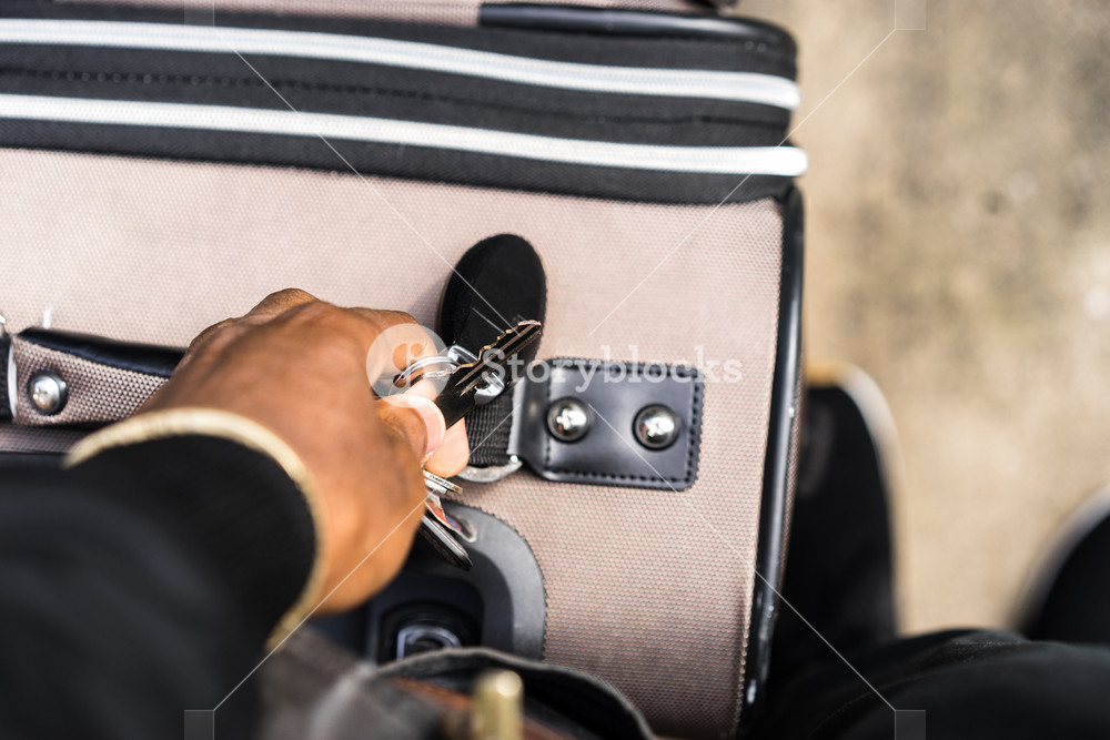 black woman holds up key next to luggage