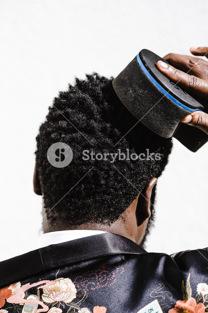 image of the back of a man's head while he brushes his hair