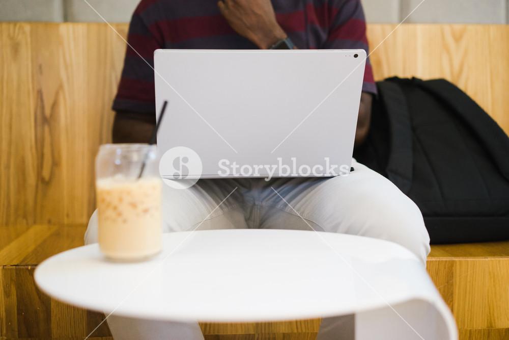 laptop in a Black man's lap