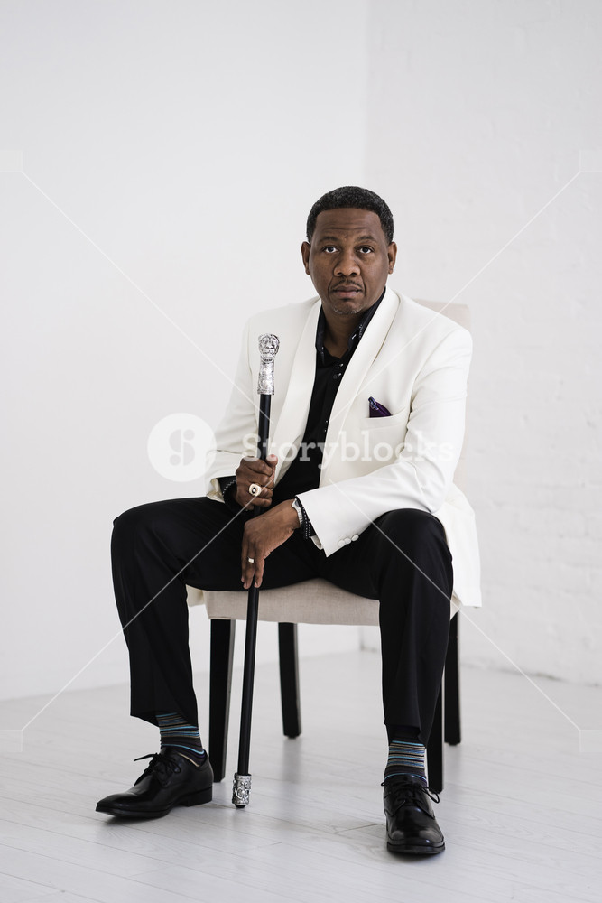 man holding a fancy cane in a white suit