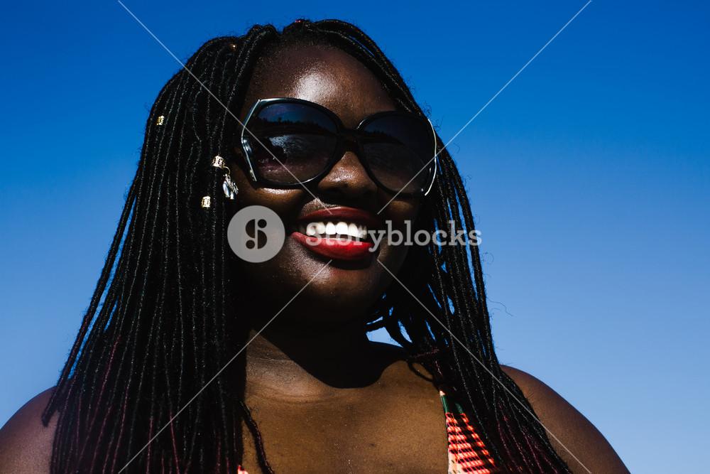 Ugandan woman with long braids smiling on the beach