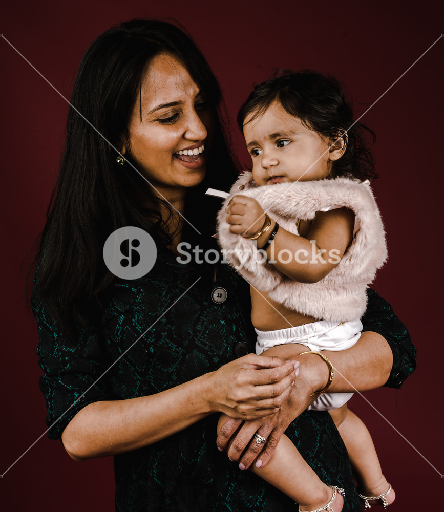 Young Indian girl being held by her Indian, mother